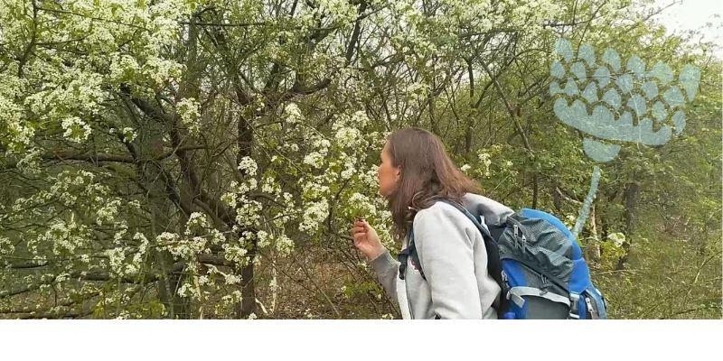 Marielle ruikt aan bloesem in het bos
